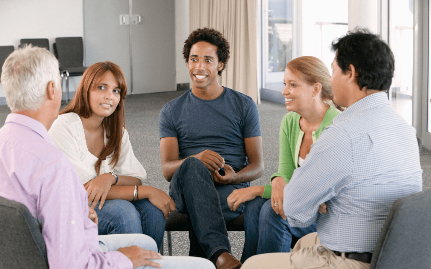 three men and two women sit in a circle for a support group