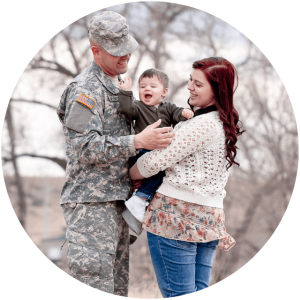 veteran stands with a woman and a baby
